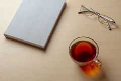 Gray diary, cup of tea, and glasses on a brown table, selective focus royalty free stock photo