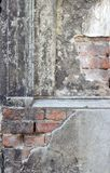 Gray, dilapidated facade with bricks. Detail of an old, gray, dilapidated facade with bricks stock image