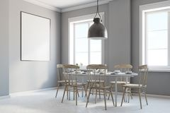 Gray dining room corner, poster. Gray dining room corner with a concrete floor, gray walls, a light wooden and white table with chairs and a framed vertical Royalty Free Stock Photography