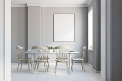 Gray dining room interior, poster. Gray dining room interior with a concrete floor, gray walls, a light wooden and white table with chairs and a framed vertical Stock Image