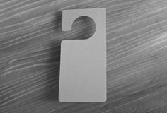 Gray door hanger. On a wooden background Royalty Free Stock Photo
