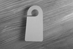 Gray door hanger. On a wooden background Stock Photo