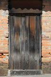Gray Door resistido em uma parede de tijolo Imagens de Stock