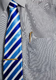 Gray Dress Shirt with Gold Pen in Pocket. A gray dress shirt with a blue and white striped tie, held on with a golden tie clip, and a gold and silver pen in the Royalty Free Stock Photography
