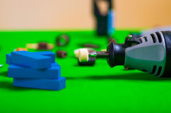 A gray drill with a small blue wooden pieces on a green background Stock Photography