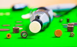 A gray drill with some drilling accessories on green background Royalty Free Stock Photos