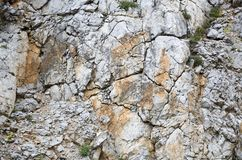 Gray dyed with red spots massive rock mass consist smaller and bigger stones and areas of plants. Massive rocks in mountain. А steep wall royalty free stock images
