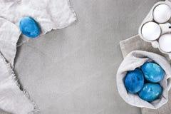 Gray Easter bakgrund med blåa ljusa ägg royaltyfri foto