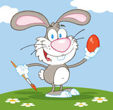 Gray easter bunny painting an egg outside Royalty Free Stock Images