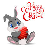 Gray Easter Rabbit sitting and holding egg. Cute cartoon Easter Bunny character with hand drawn lettering. Royalty Free Stock Photo