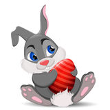 Gray Easter Rabbit sitting and holding egg. Cute cartoon Easter Bunny character. Stock Images