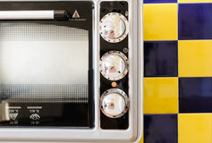 Gray Electric stove in the kitchen. Electric Oven gray-black color on a background of blue-yellow tile Royalty Free Stock Photos