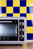 Gray Electric stove in the kitchen. Electric Oven gray-black color on a background of blue-yellow tile Stock Images