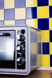 Gray Electric stove in the kitchen. Electric Oven gray-black color on a background of blue-yellow tile Stock Image