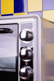 Gray Electric stove in the kitchen. Electric Oven gray-black color on a background of blue-yellow tile Royalty Free Stock Images