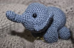 Gray elephant crochet sitting on a knitted texture stock photos
