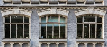 Gray facade of a historic building with three arched windows. Facade of an old brick building with three arched windows Royalty Free Stock Images