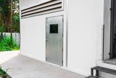 Gray Factory Door de plata en la pared blanca Foto de archivo