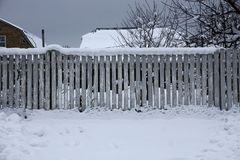 Gray fence of thin wooden boards in white snow on a rural street. Gray long fence of thin wooden boards in white snow on a rural street stock images