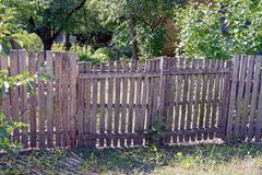 Gray fence with wicket gate in the grass Royalty Free Stock Photo