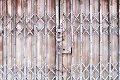 Gray folding steel door in interlace patterns for background and three rusty old locked royalty free stock photos