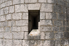 Gray Fortified Wall with a Loophole. Detail of a loophole (rifle slit) in a grey fortified wall. Austrian fortress Stock Photo
