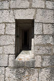 Gray Fortified Wall with a Loophole. Detail of a loophole (rifle slit) in a grey fortified wall. Austrian fortress Stock Image