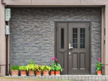 Free Gray Front Door With Small Square Decorative Windows And Flower Pots In Fron Of It Royalty Free Stock Image - 149634026