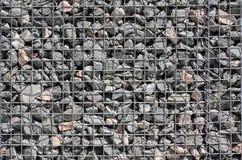 Grey ground stone rubble background of many small stones. Gray ground stone rubble background of many small stones behind an iron grid stock photography