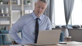 Gray Hair Businessman avec douleurs de dos spinales se reposant au travail banque de vidéos