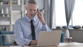 Gray Hair Businessman Discussing Project tout en parlant au téléphone banque de vidéos