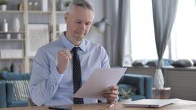 Gray Hair Businessman Excited après lecture des documents banque de vidéos