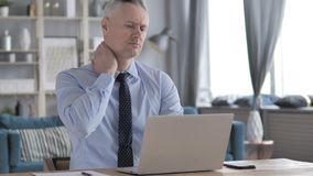 Gray Hair Businessman fatigué avec douleur cervicale travaillant sur l'ordinateur portable banque de vidéos