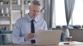Gray Hair Businessman Reading Documents en el trabajo almacen de metraje de vídeo