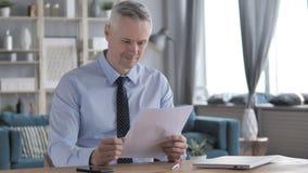 Gray Hair Businessman Reading Documents positivo, contrato almacen de video
