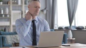 Gray Hair Businessman stanco con dolore al collo che lavora al computer portatile video d archivio