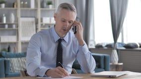 Gray Hair Businessman Talking en el teléfono y la información de la escritura almacen de video