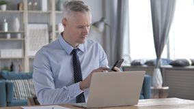 Gray Hair Businessman Using Smartphone nel luogo di lavoro archivi video