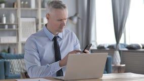 Gray Hair Businessman Using Smartphone sur le lieu de travail clips vidéos
