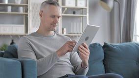Gray Hair Man Browsing Internet sulla compressa mentre sedendosi sullo strato stock footage
