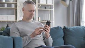 Gray Hair Man Browsing su Smartphone, facendo uso di Internet stock footage