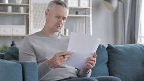 Gray Hair Man Reading Documents tout en se reposant sur le sofa, ?critures banque de vidéos