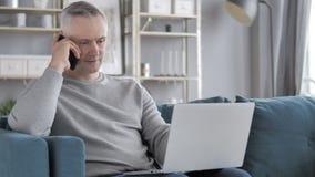 Gray Hair Man Talking en el teléfono mientras que trabaja en el ordenador portátil metrajes