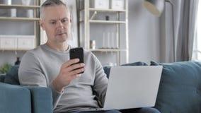 Gray Hair Man Using Smartphone en Laptop voor het Werk stock video