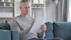 Gray Hair Man Working op Documenten terwijl het Zitten op Bank stock video