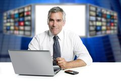 Gray hair tv news screen presenter laptop smiling. White desk Royalty Free Stock Photo
