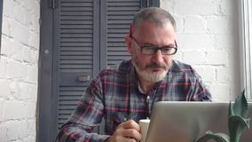 Gray-haired bearded male accountant working at home behind a laptop, making a report against the backdrop of a minimalist interior stock video footage