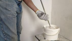 A gray-haired bearded man mixes white paint in a bucket by a stick and pours into the container. A gray-haired bearded man mixes white paint in a bucket by a stock video