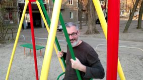 Gray-haired bearded man riding on a swing, rejoices and smiles, concept of a happy childhood.  stock video footage