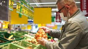 Gray-haired elderly pensioner man buys onions in a grid in a supermarket. Shopping during Quarantine Coronavirus Covid